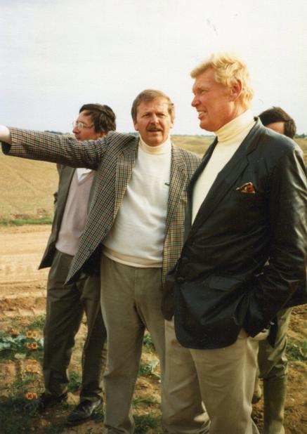 用地を歩き、計画をフォン・ヘギー(右)に説明するシノー(中央)。